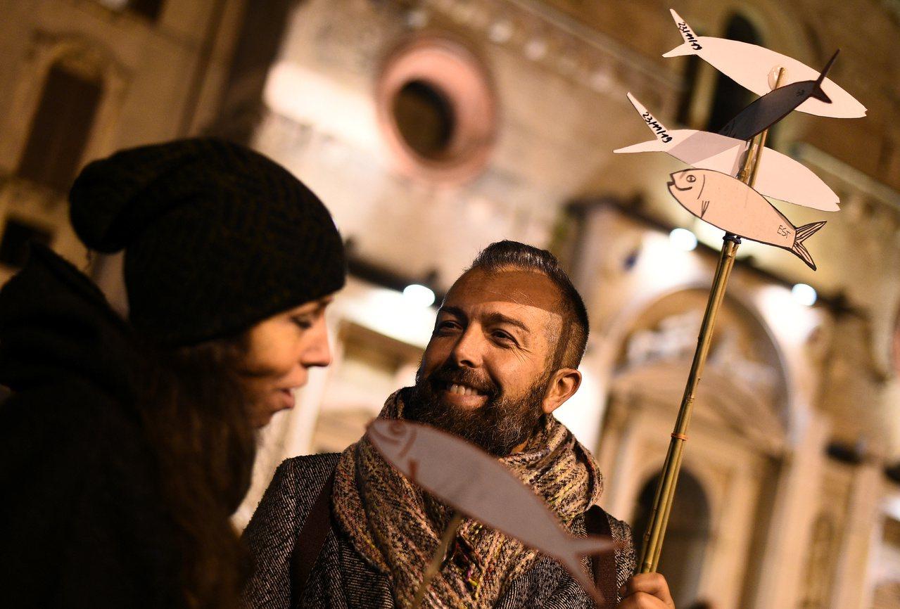 民眾舉著用紙板等材料做成的魚型標誌物參加集會。(路透)