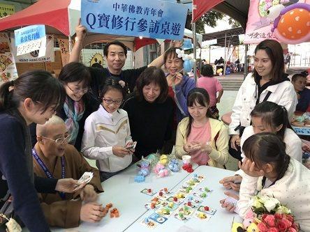 中華佛教青年會理事長 開善法師趁中午休息時間與小朋友們玩桌遊、做Q寶布偶。 慈法...