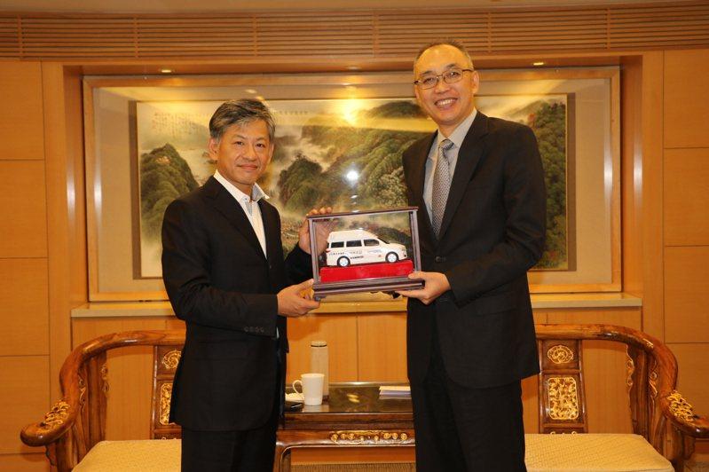 新北副市長謝政達(右起)回贈復康巴士模型車,給新潤、華潤建設董事長黃文辰 。圖/新北社會局提供