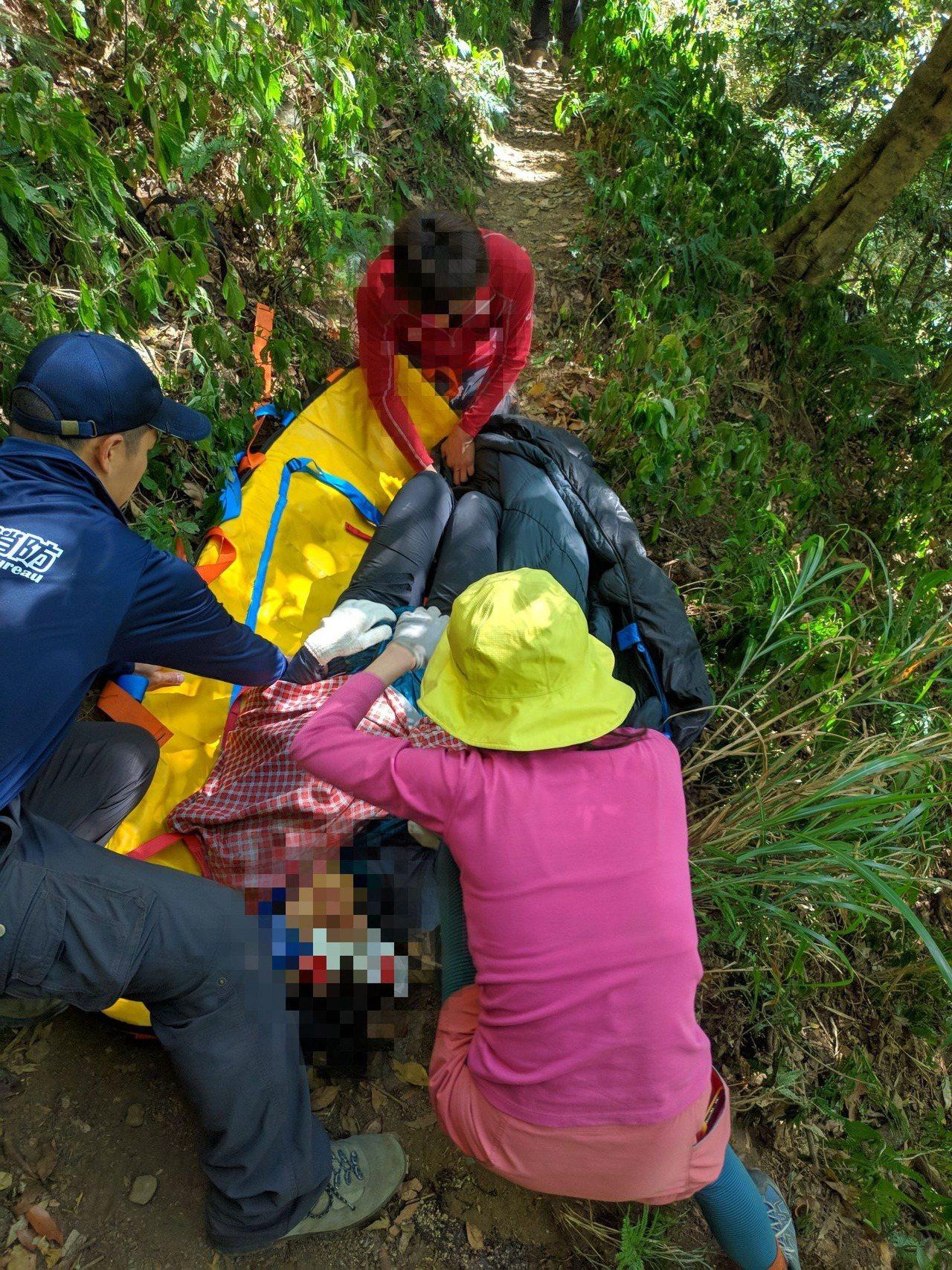 消防人員協助抬溫女到較平坦空曠的河床處,方便直升機執行吊掛作業。記者陳玫伶/翻攝