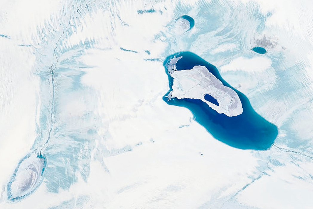 科學家觀察到格陵蘭冰蓋融化形成的湖泊快速乾涸。圖為格陵蘭冰蓋融化的衛星照片。 歐...