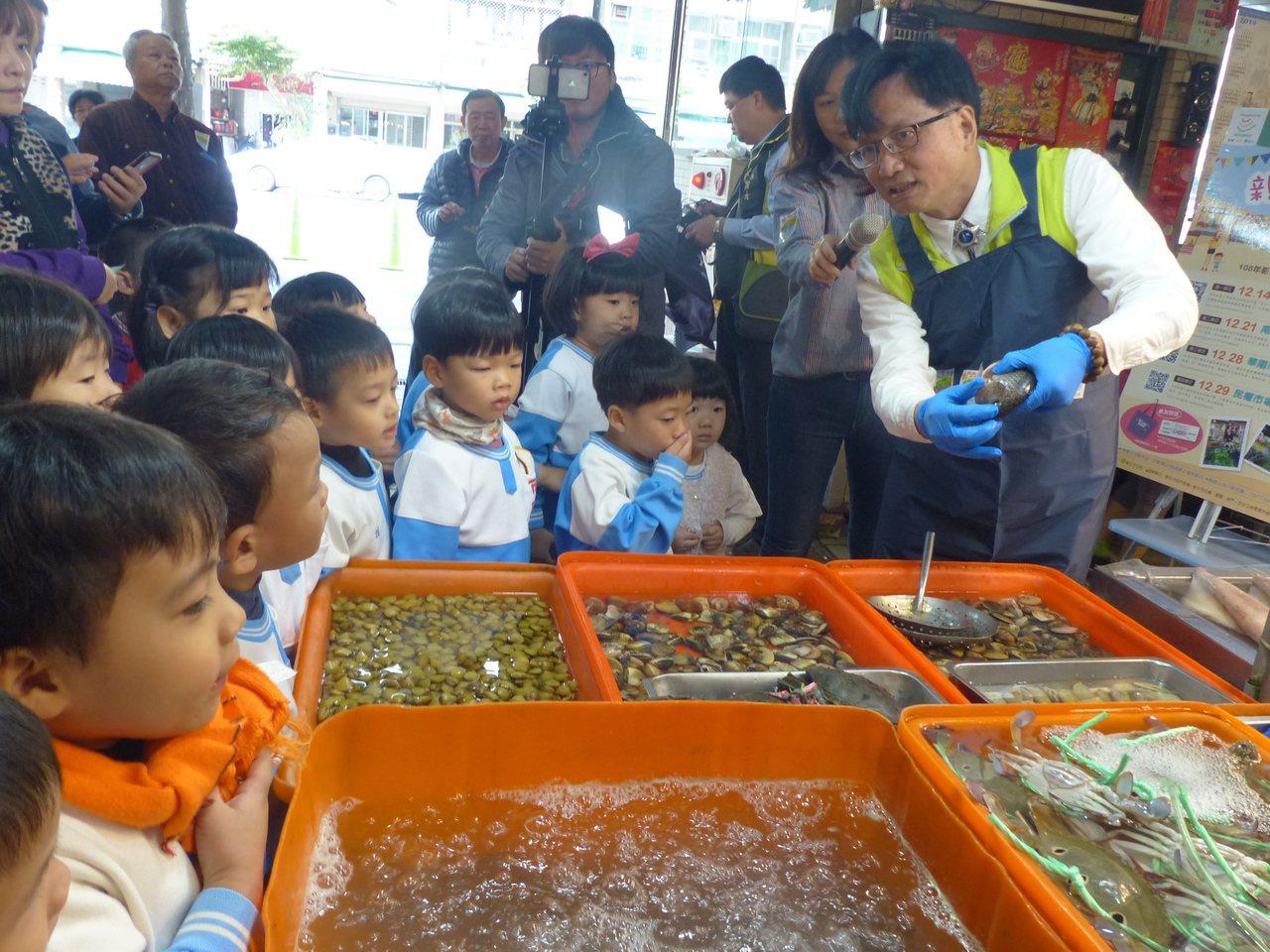 彰化市長林世賢教導小朋友如何選購鮮魚。記者劉明岩/攝影