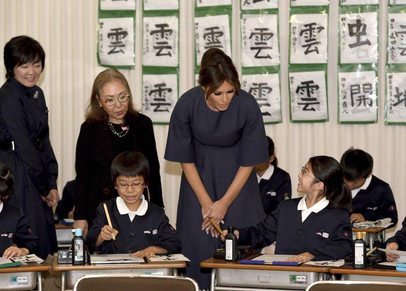 日本學生在PISA調查中的閱讀能力排名大跌,令教育界相當震驚。圖為美國第一夫人梅蘭妮亞(中)前年訪問日本時參觀學生書法課。(美聯社)