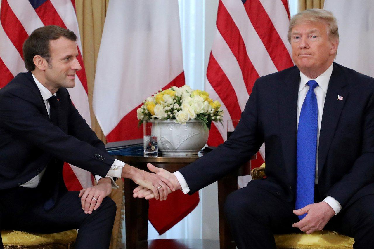 美國總統川普(右)3日和法國總統馬克宏在倫敦舉行雙邊會議,照片可見川普並未握住馬...