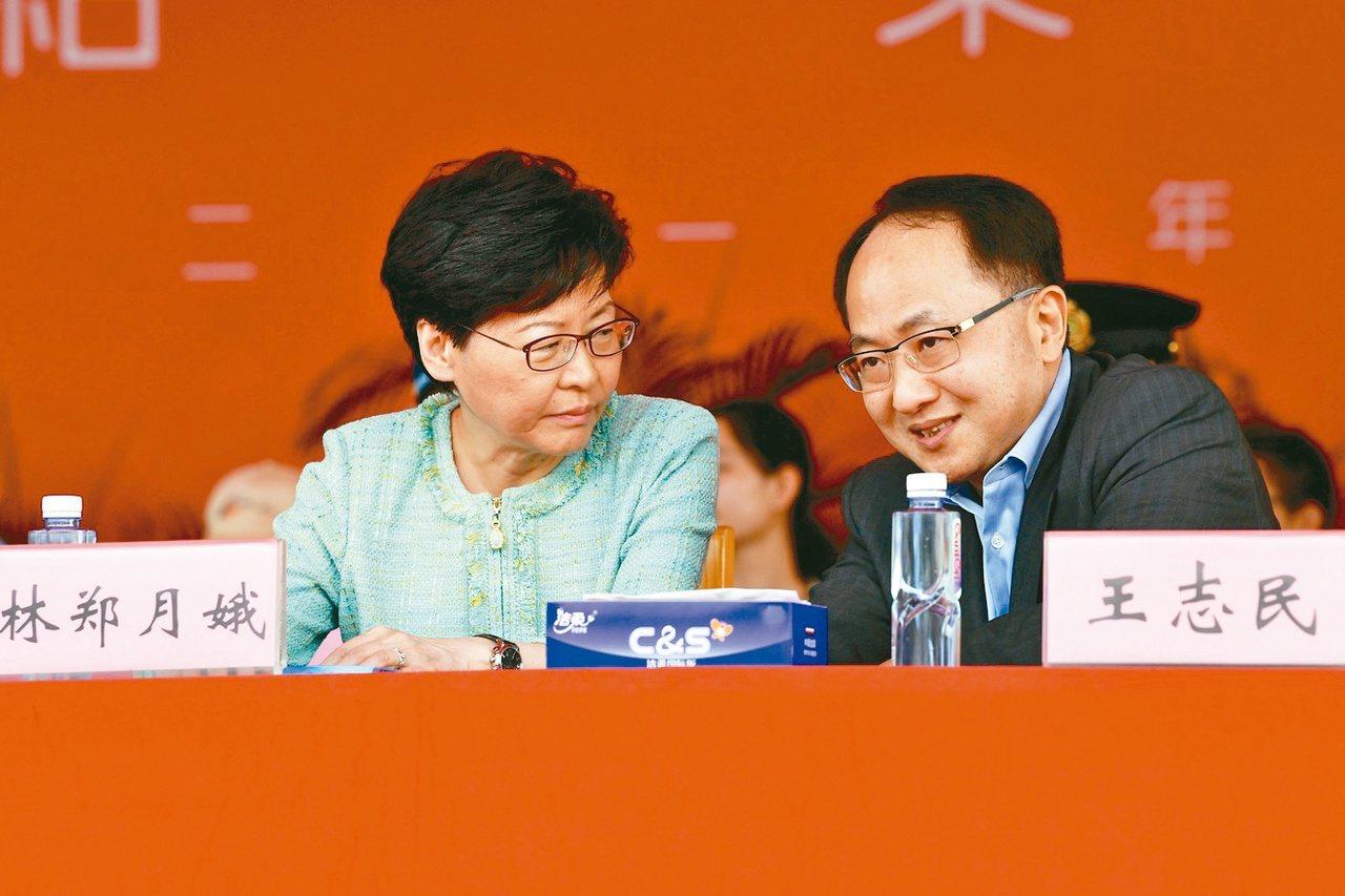 香港特首林鄭月娥(左)、中聯辦主任王志民(右)今年七月一起出席香港青少年軍事夏令...