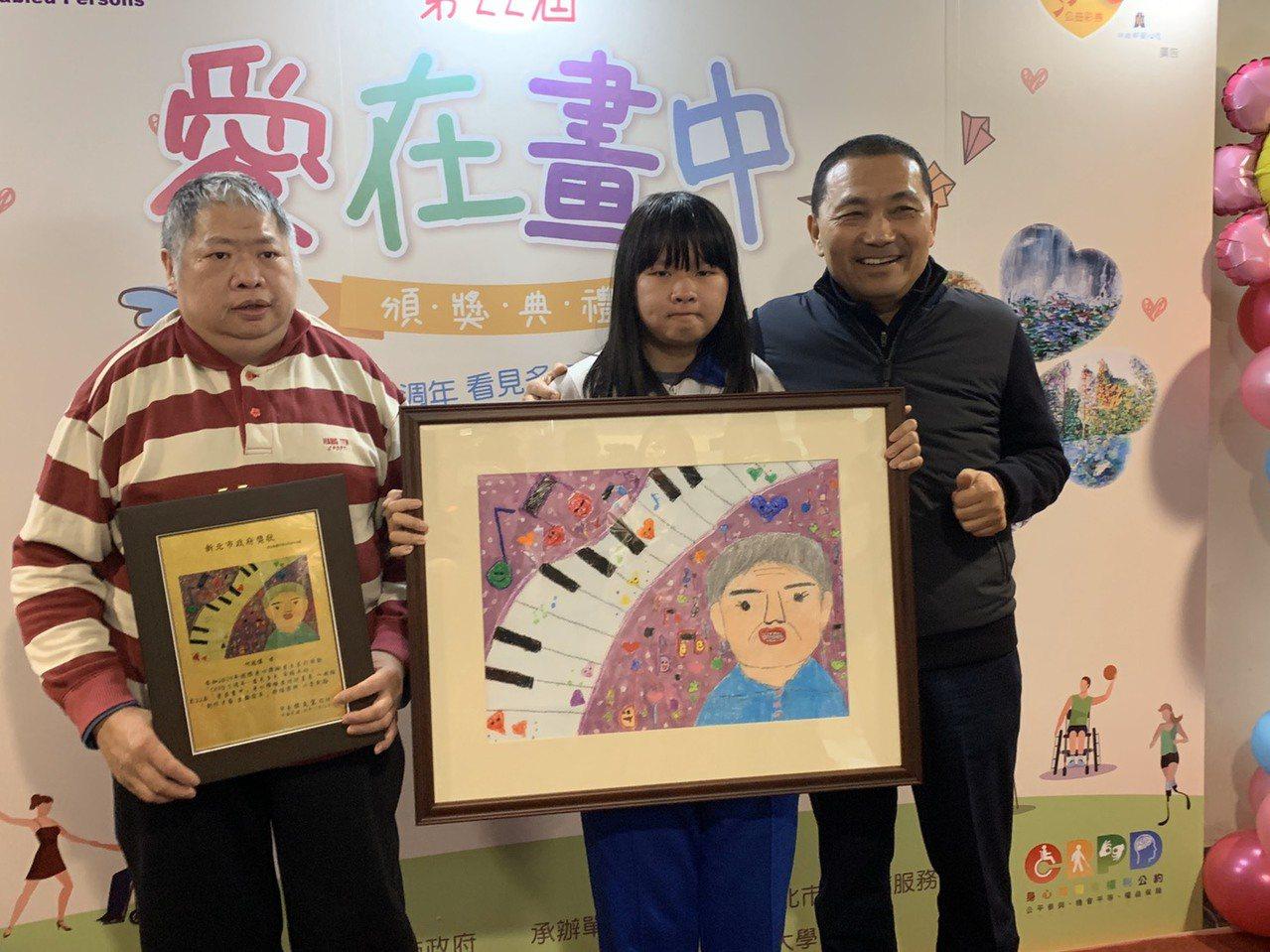 何冠儀(中)以「彈鋼琴給阿嬤聽」獲獎,昨天在爸爸(左一)等人陪同下出席,她想到阿...