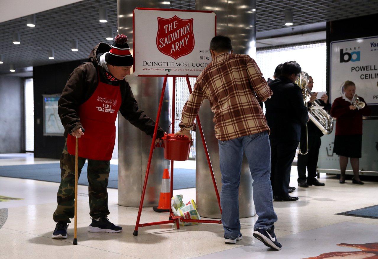研究顯示,16年來,慈善捐款的家庭少了2000萬個。圖為一名男子捐錢給救世軍。 ...