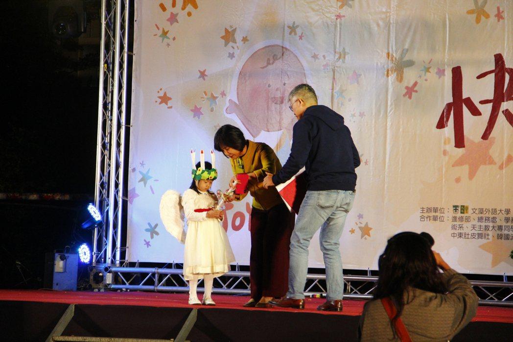小聖路濟亞將手中的光傳遞給舞台上的陳美華校長。 文藻外大/提供。