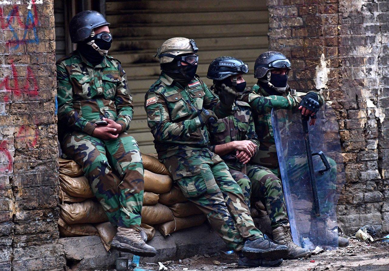 伊拉克鎮暴警察1日處理首都巴格達市中心的示威後,在一處街道稍微休息。阿聯《全國報...
