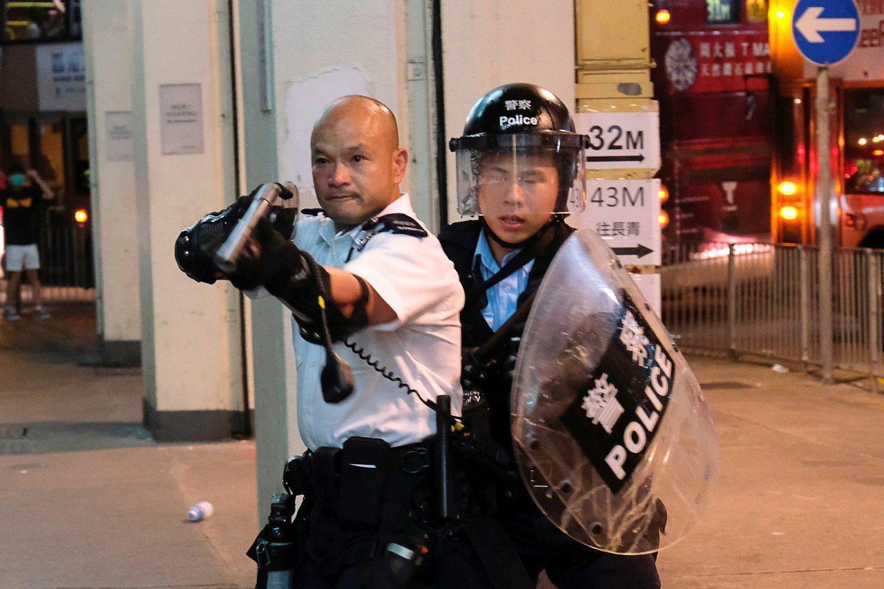 圖為光頭警長持霰彈槍瞄準示威者。路透資料照片
