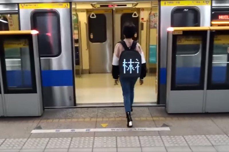 有網友PO出一段影片,一名女乘客背著裝有跑馬燈的背包,上頭還顯示著「林祖罵腳痛」5個字,讓網友看了笑翻。 圖/爆廢公社