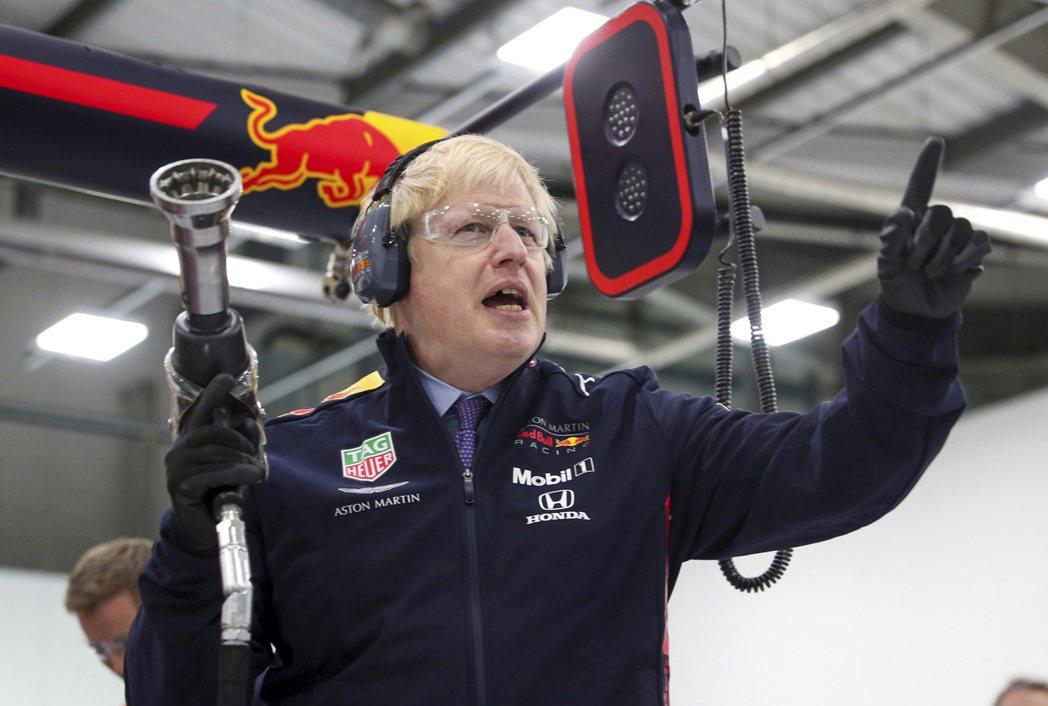 英國首相強生4日參訪Red Bull在英格蘭一處賽車設施,全副武裝準備一部F1賽...