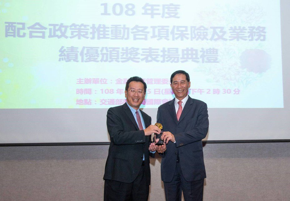 台灣人壽總經理莊中慶(右)代表公司,接受金管會主委顧立雄(左)頒發獎座。圖/台灣人壽提供