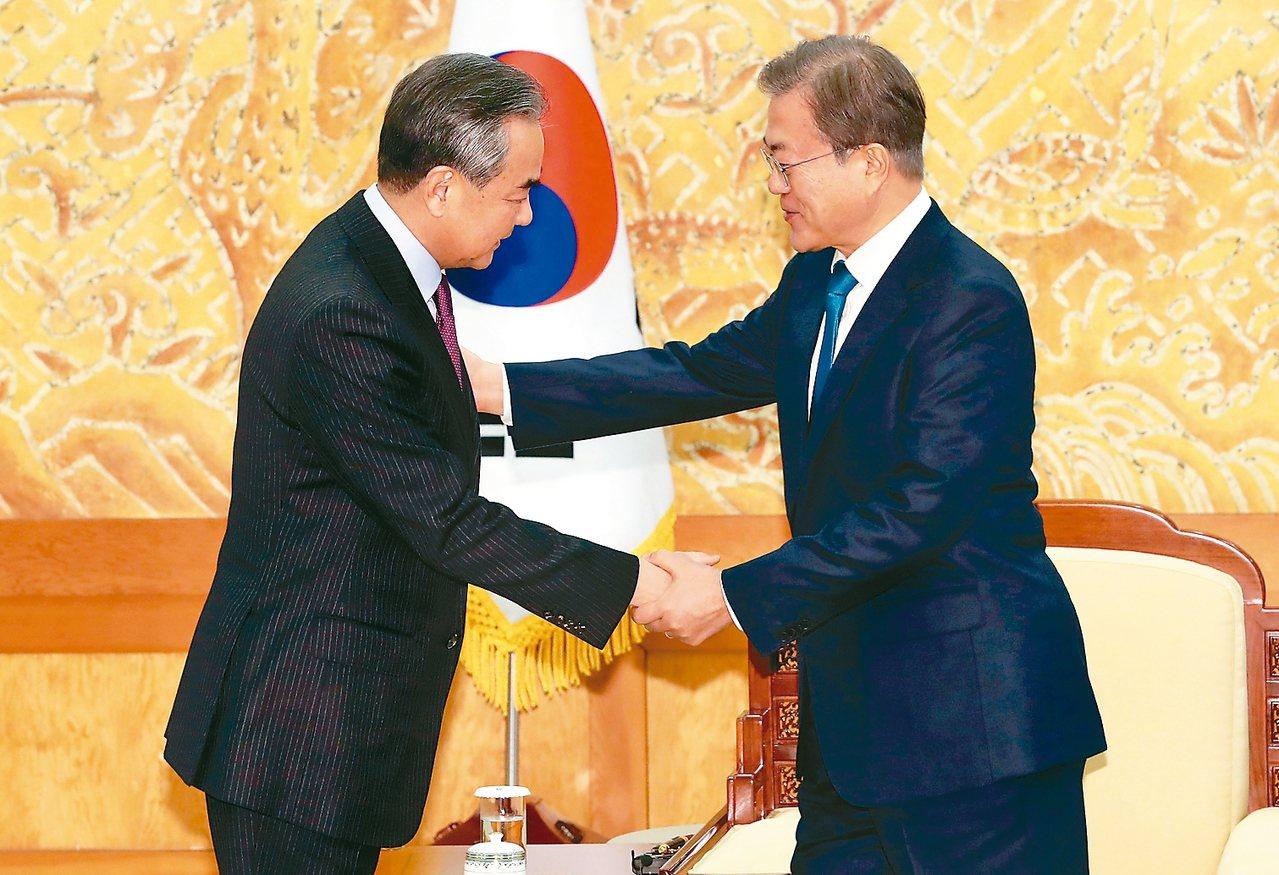 南韓總統文在寅(右)五日下午在青瓦台會見大陸國務委員兼外長王毅,力促加強雙邊對話...
