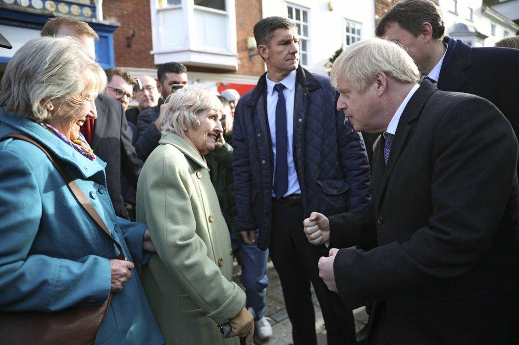 英國大選在即,首相強生(右)也上街拉票。 (美聯社)