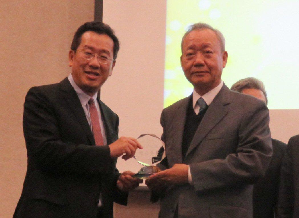 金管會主委顧立雄頒發獎座,由臺灣產物保險總經理宋道平(右)代表領獎。 臺產/提供