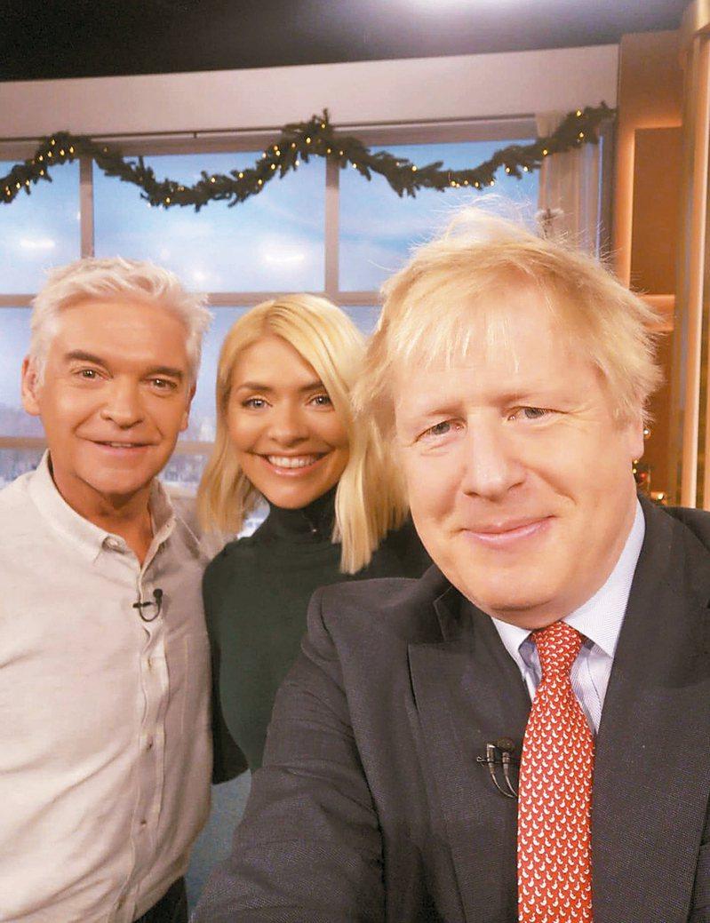 英國首相強生(右)自拍時使用的顯然是華為智慧手機。 美聯社