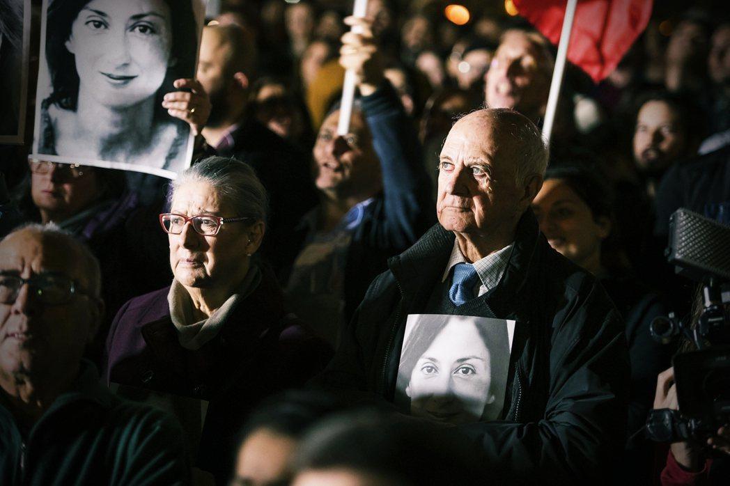 從11月開始的街頭示威,葛莉齊亞的父母也抱著女兒的照片現身人群當中。 圖/美聯社