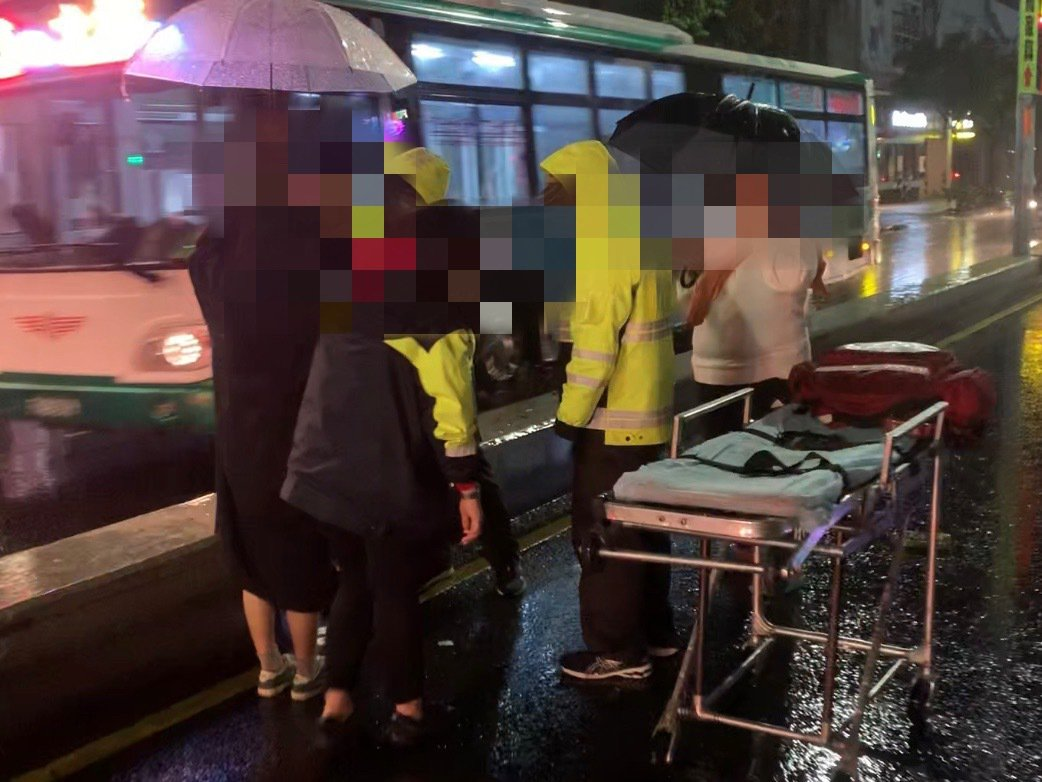 一旁許多目擊車禍的民眾,立即上前替傷者撐傘,等待救護車前來。圖/讀者提供