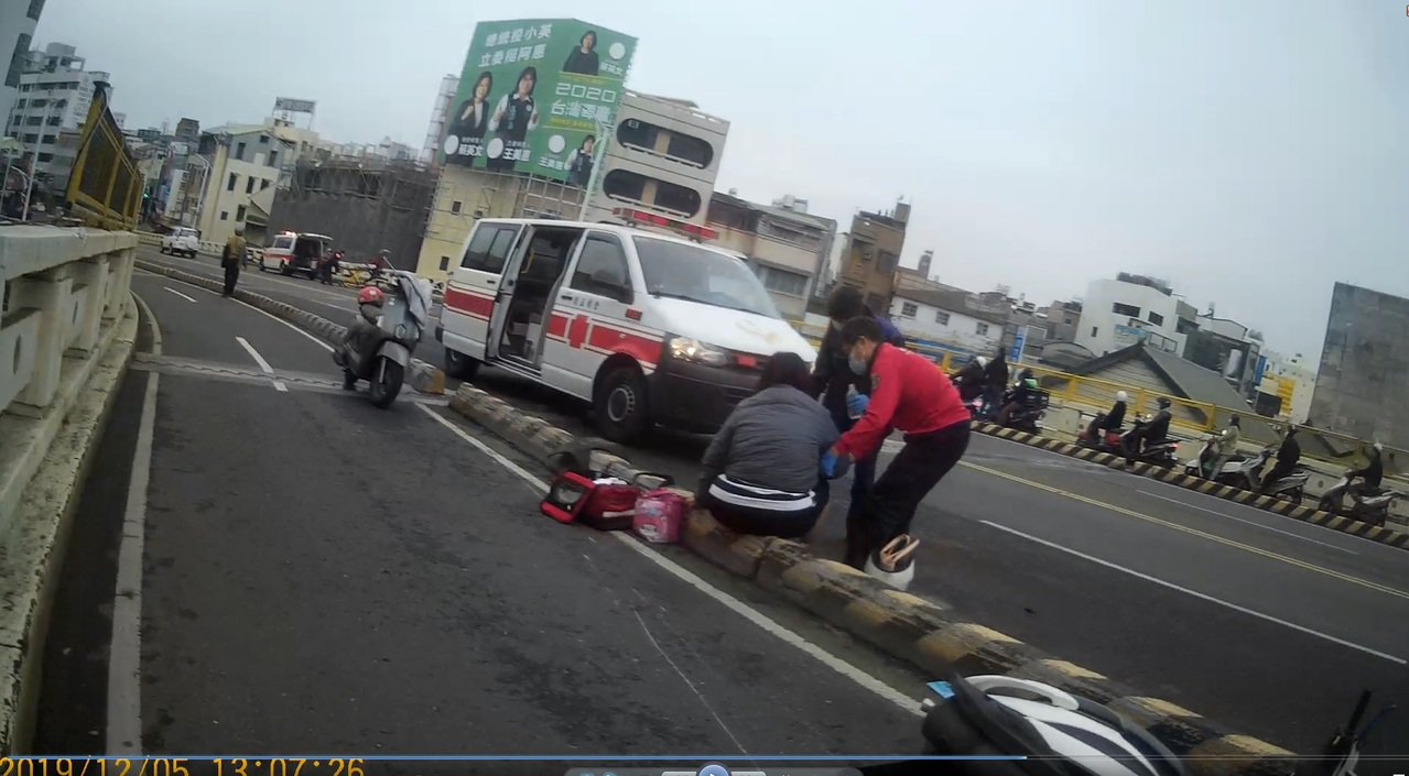 吳女車禍後坐在分隔島上,接受救護員救治。圖/讀者提供