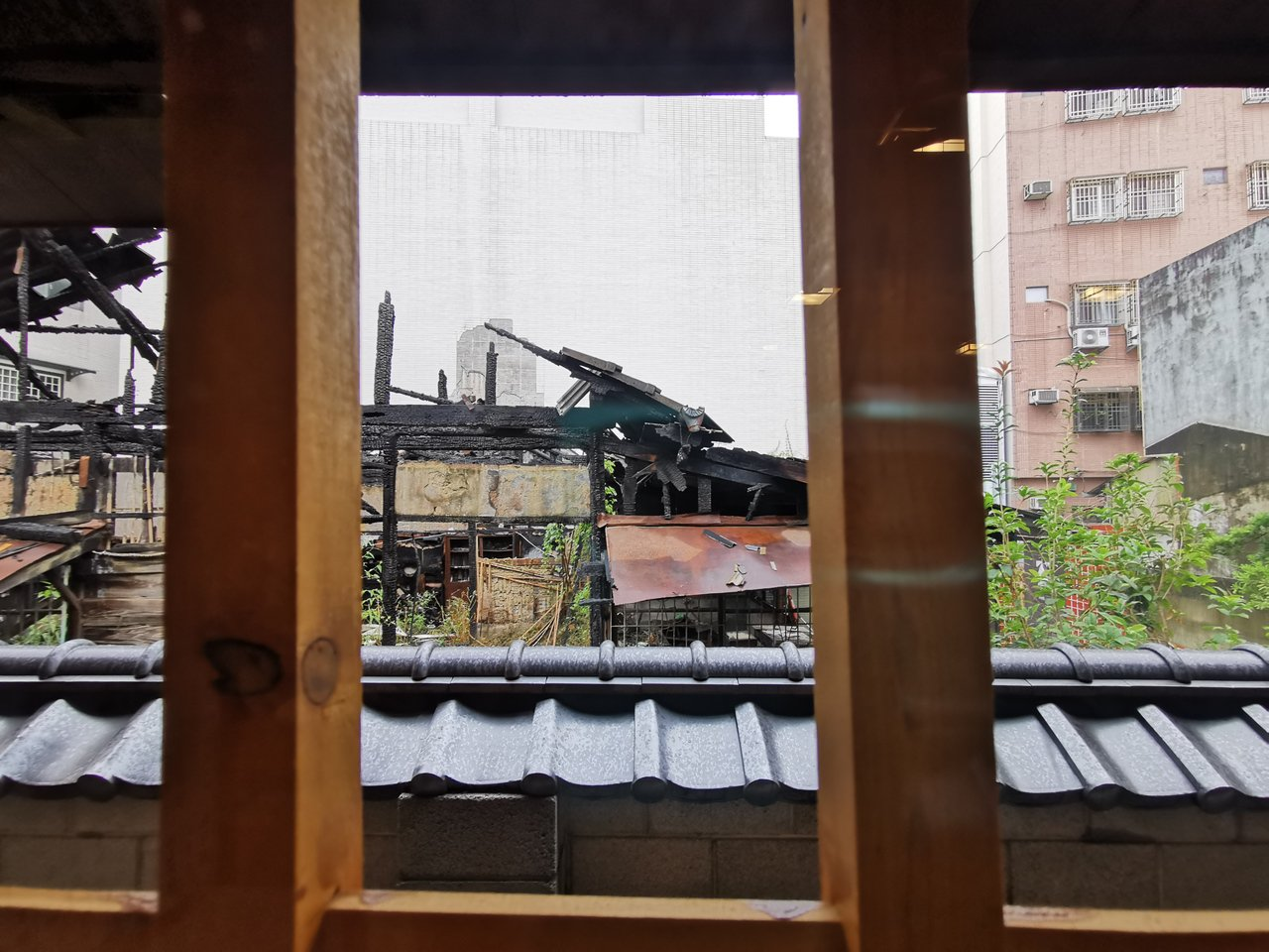 天理教嘉義東門教會,受去年隔鄰民宅失火波及,窗外還可見隔鄰燒毀後的屋瓦。記者卜敏...