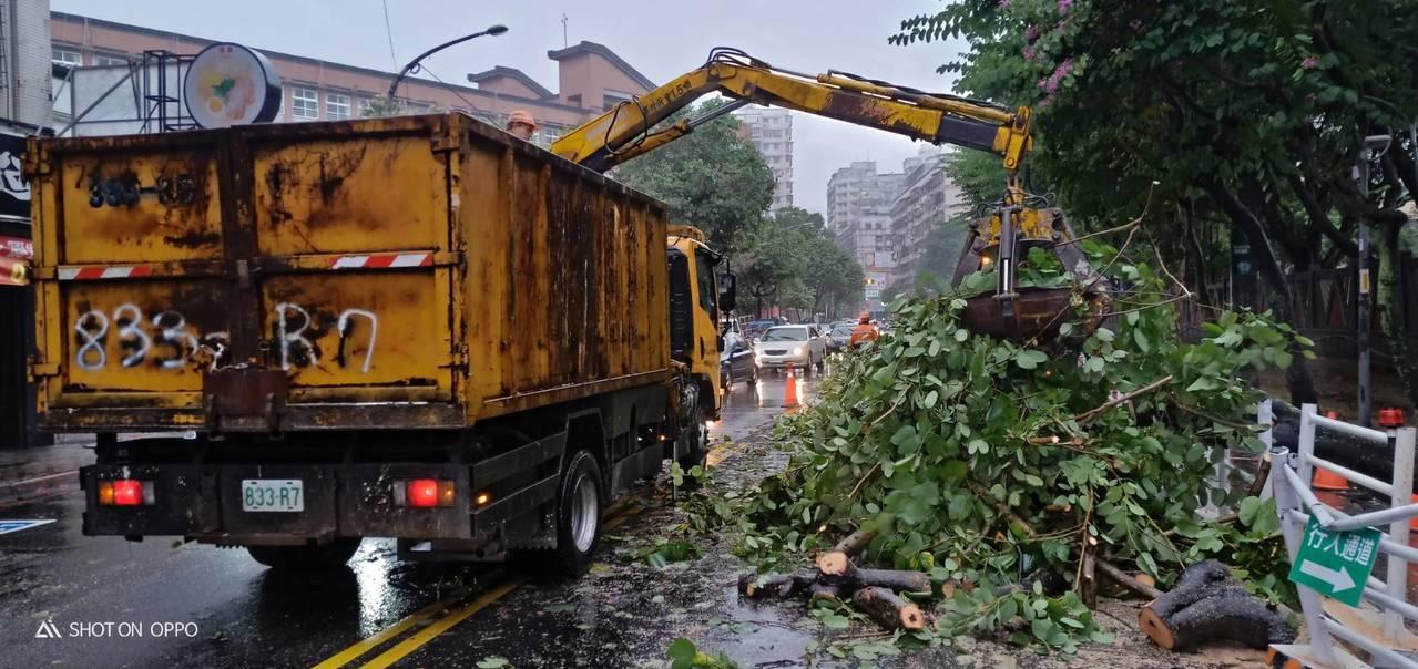 土城區公所清潔隊員運用機具切割樹根以利清運。圖/警方提供