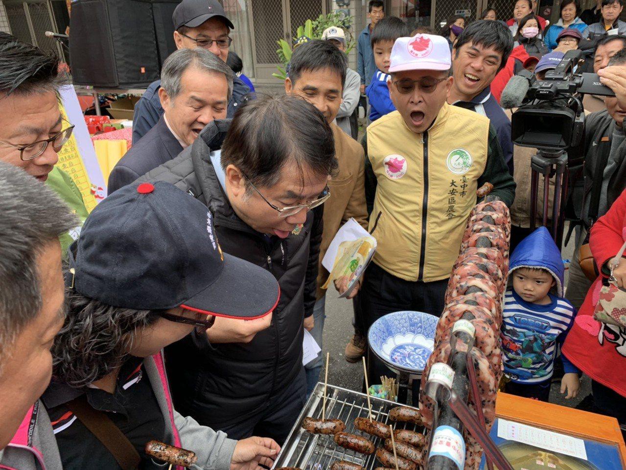 台南市長黃偉哲(中)今天出席西港胡麻節,體驗古早「打香腸」遊戲。圖/農業局提供