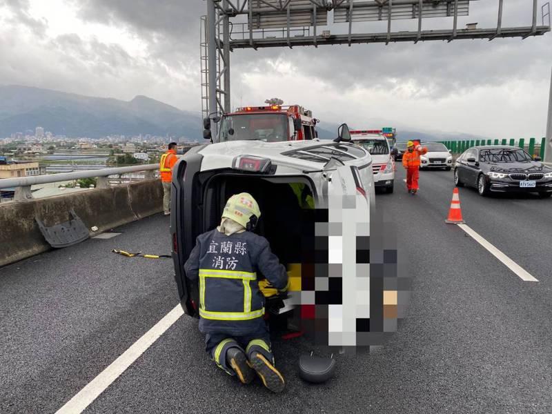 國道五號34.6公里、即礁溪到宜蘭路段,今天上午傳出車禍,一輛小客車不明原因側翻路上,車上一名婦人受困,消防局緊急救出送醫。圖/宜蘭縣消防局提供