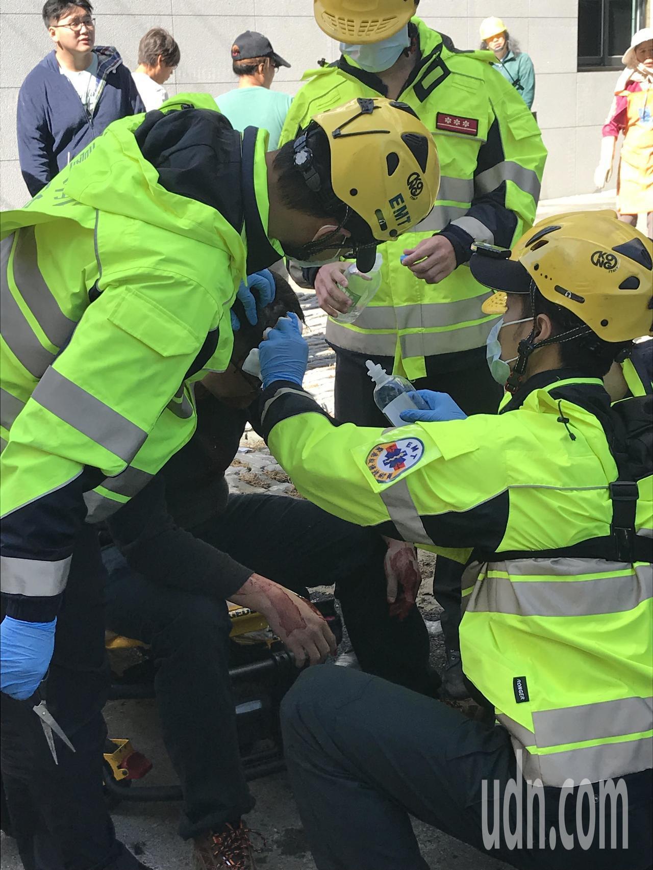 黃男頭部疑遭銳器劃傷,救護員現場替黃男清理傷口。記者林佩均/攝影
