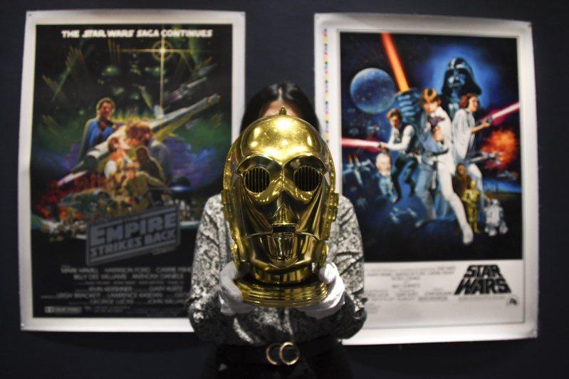 蘇富比電影海報顧問馬強特表示,他們花了超過一年的時間收集這些拍品。(美聯社) Britain Auction Sotheby's A Sotheby's employee holds a C-3PO helmet of 1983 as part of the Star Wars auction in London, Friday, Dec. 6, 2019. Sotheby's will now host its second sale dedicated to 'Star Wars' collectibles, titled 'Star Wars Online'. (AP Photo/Alberto Pezzali)