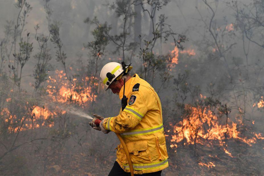 澳洲一名消防員正和灌木叢大火奮戰,當局直言只有大雨才能滅火。(法新社)