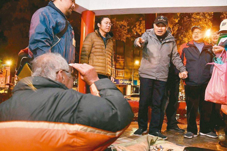 新北市長侯友宜(右2)前晚到板橋四維公園探視街友,提醒寒流來了,要注意保暖,同時也致贈生活物資。 圖/新北新聞局提供