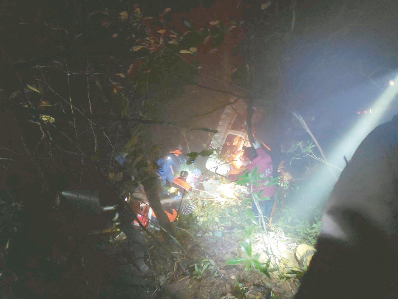 合歡山公路昨天晚間發生大貨車墜谷,救難人員搶救受困的三名乘客。 圖/南投縣消防局...