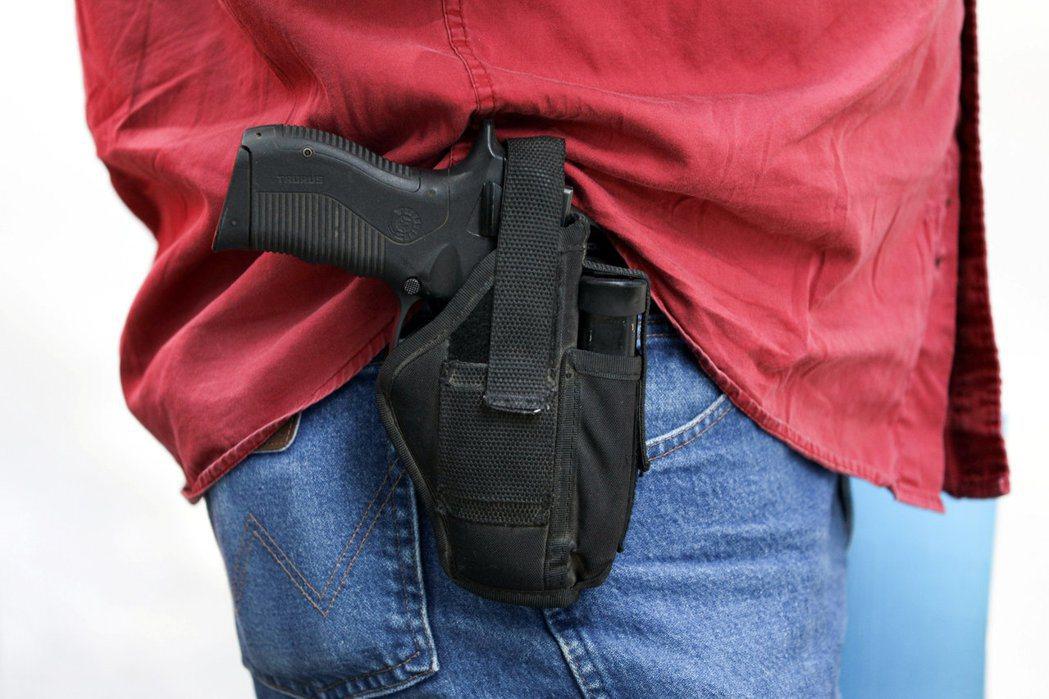 公開攜槍就是讓旁人看到槍枝,而且手不在扣扳機位置上。 (路透)