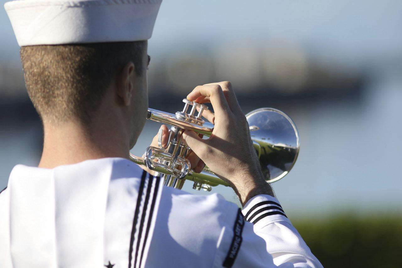 7日是日本偷襲珍珠港78周年,一名水兵在紀念會上吹號。(美聯社)