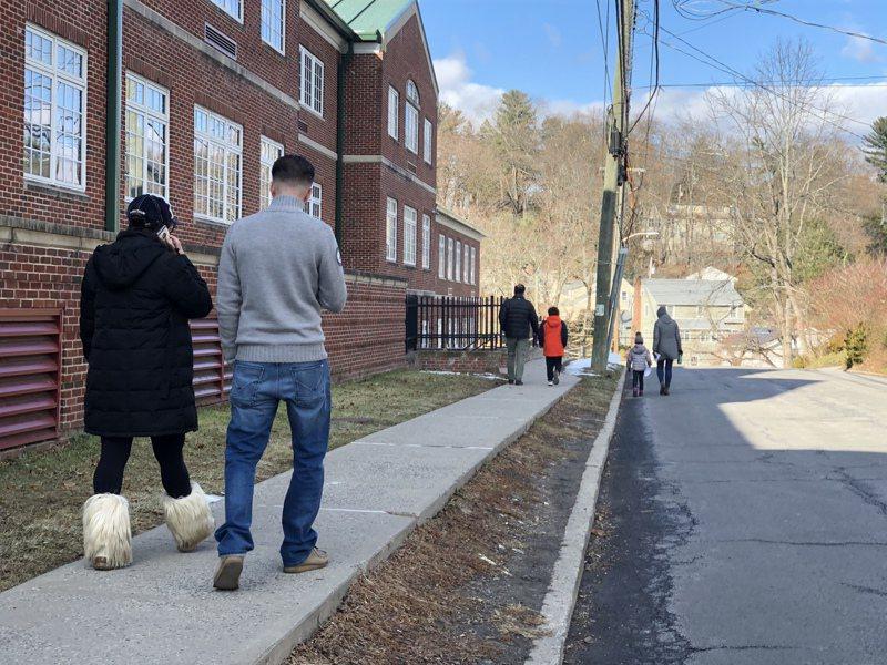 有家長帶著孩子向小鎮的拜福路小學(Bedford Road School)走去,這是案發後舉辦的第二場心理輔導,人們互相擁抱。 記者張晨/攝影