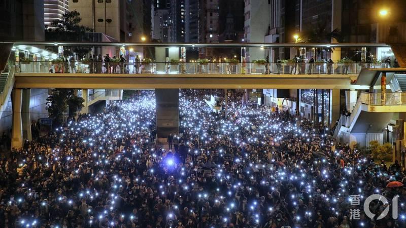 民陣於今(8日)發起「12.8國際人權日」遊行,隊伍準時於下午三時出發。由於遊行人數多,龍尾至六時仍未離開高士威道中央圖書館對出位置。入夜後,不少遊行人士亮起手機燈,形成一條延綿灣仔、金鐘的長長燈河。 圖/摘自香港01