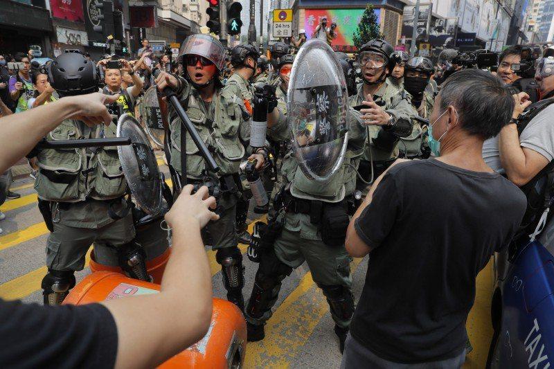 民陣遊行前,港警發文譴責網上煽動破壞社會行為。圖為日前港警截查黑衣人,雙方對峙。美聯社