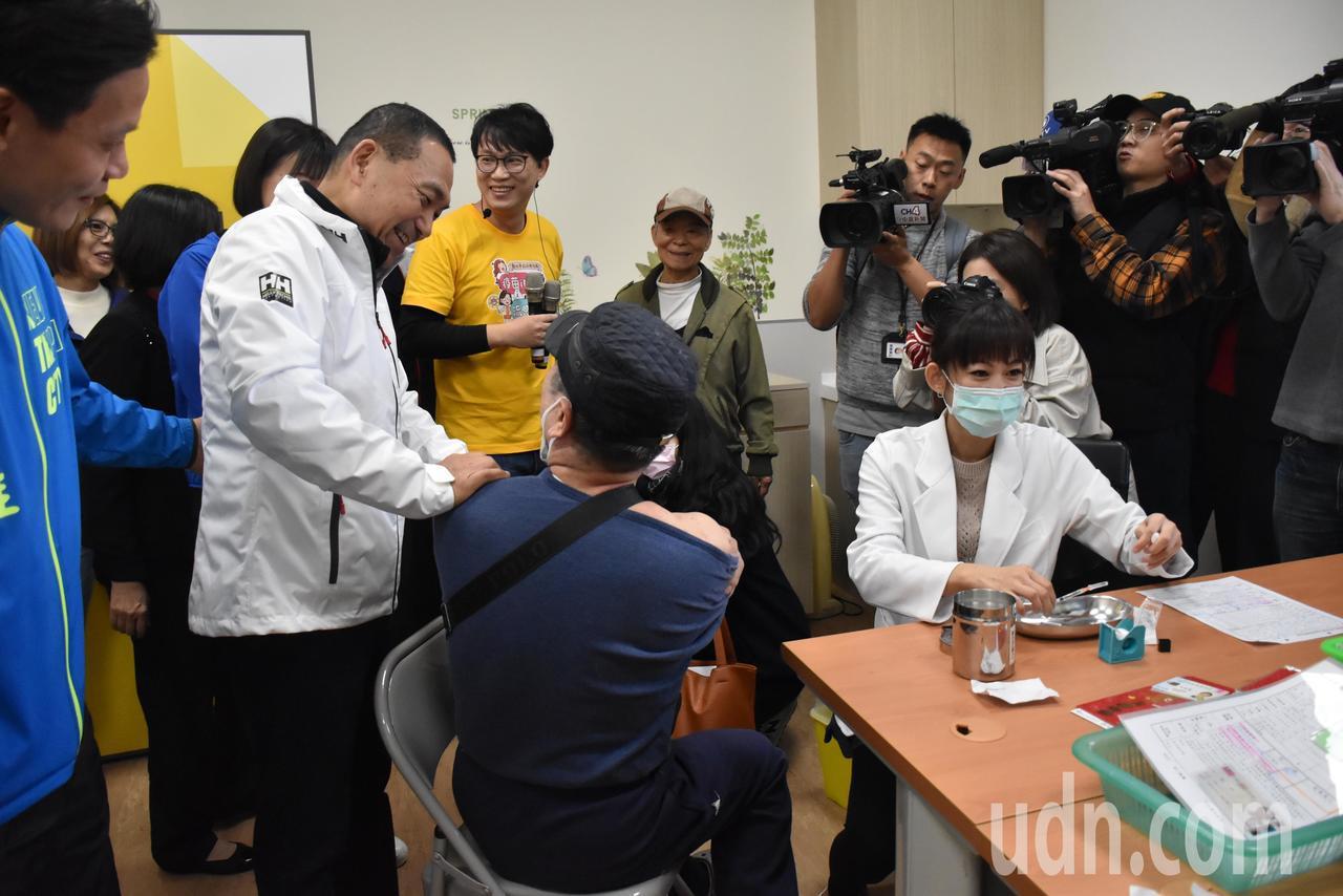 一位正在接種的阿伯(左二)熱情邀請侯友宜(左一)一同接種疫苗,侯友宜笑說自己還沒...