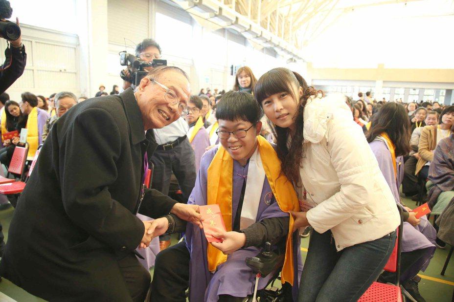 南華大學昨天上午舉辦一年一度的新生成年禮,南華大學校長林聰明(左)特別為應用社會學系患有腦性麻痺的陳姓同學(中)進行再加禮披巾及三加禮儀式。圖/南華大學提供