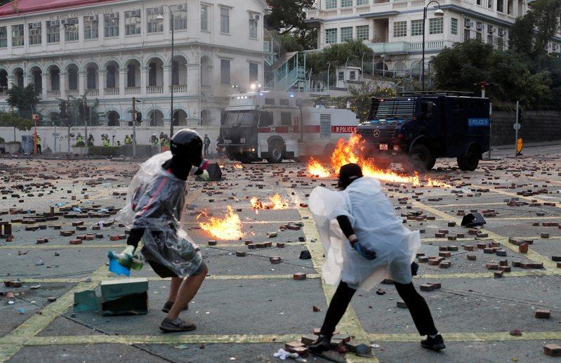 紐約時報報導,已有200多名香港反送中示威者潛逃至台灣。圖為香港11月17日的反政府示威中,部分示威者朝警車扔擲汽油彈。路透
