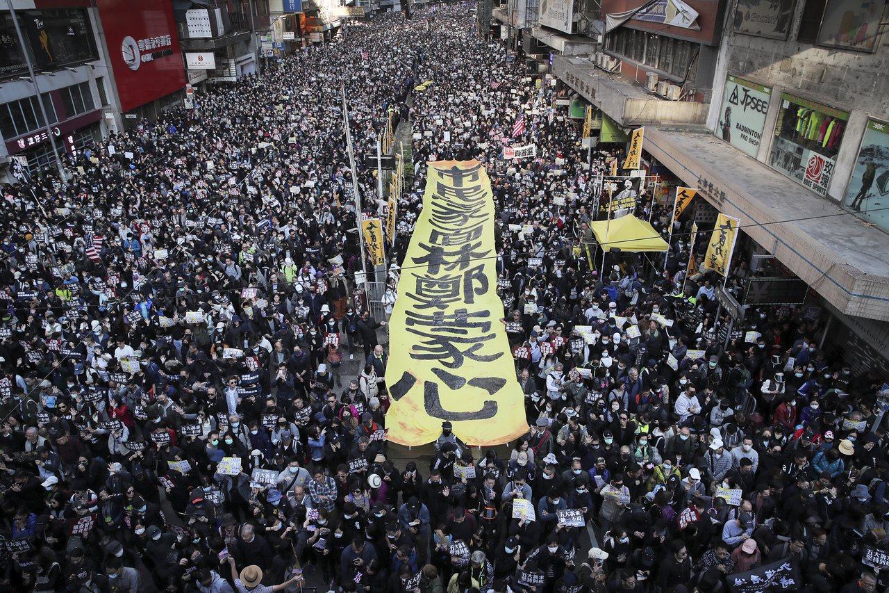 香港民陣今天(8日)下午發起「國際人權日遊行」,遊行隊伍中有人舉著「市民蒙面、林...