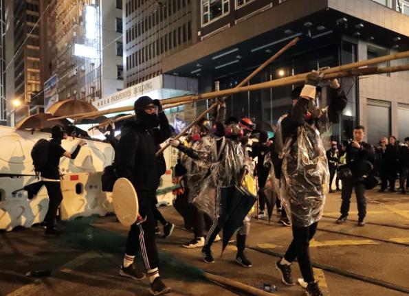 香港黑衣人在遮打道和畢打街附近架設路障並組成傘陣,與警方對峙。(美聯社)
