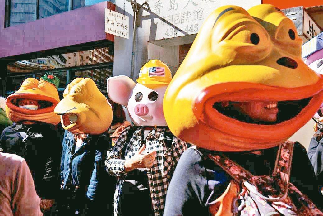 昨天遊行中,有民眾戴連登豬(右二)和佩佩蛙頭套,兩者皆是反送中示威者用來表達抗爭...