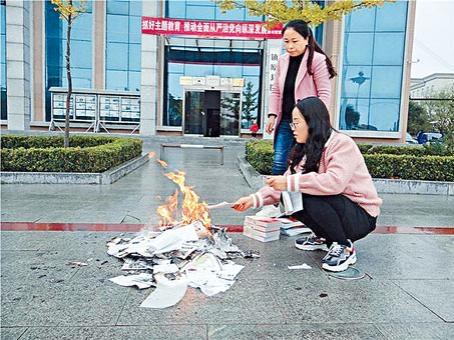 在中共開展全國中小學圖書館圖書審查清理專項行動之際,兩名人員在鎮原縣圖書館門口焚...