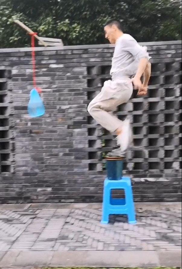 網上瘋傳一段「輕功水上飄」短片,一名男子從地面跳起,踏在水面上後再凌空踢向水袋後落地。圖/取自西瓜視頻