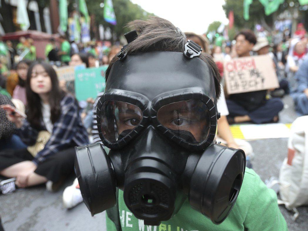 南韓民眾9月間舉行要求政府對抗氣候變遷的抗議活動,一名小學生戴防毒面具參與。美聯...