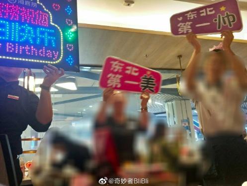 大陸知名連鎖火鍋品牌海底撈服務生拿出閃爍著生日快樂的燈牌,齊聚為顧客大唱生日快樂歌。圖/取自微博