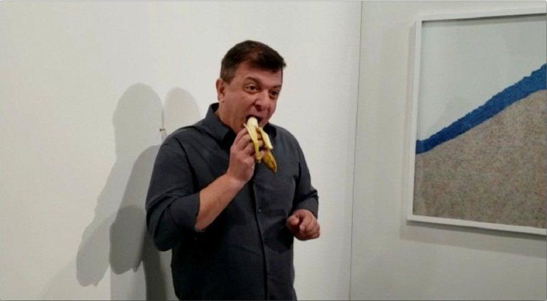 藝術家卡特蘭用大力膠帶把香蕉貼在牆上,創作出限量3套的奇葩藝術品「喜劇演員」,其中一套7日下午被表演藝術家達圖那以行為藝術之名,當眾吃個乾淨,事後受訪坦言絕不會感到抱歉。 路透/Ronn Torossian
