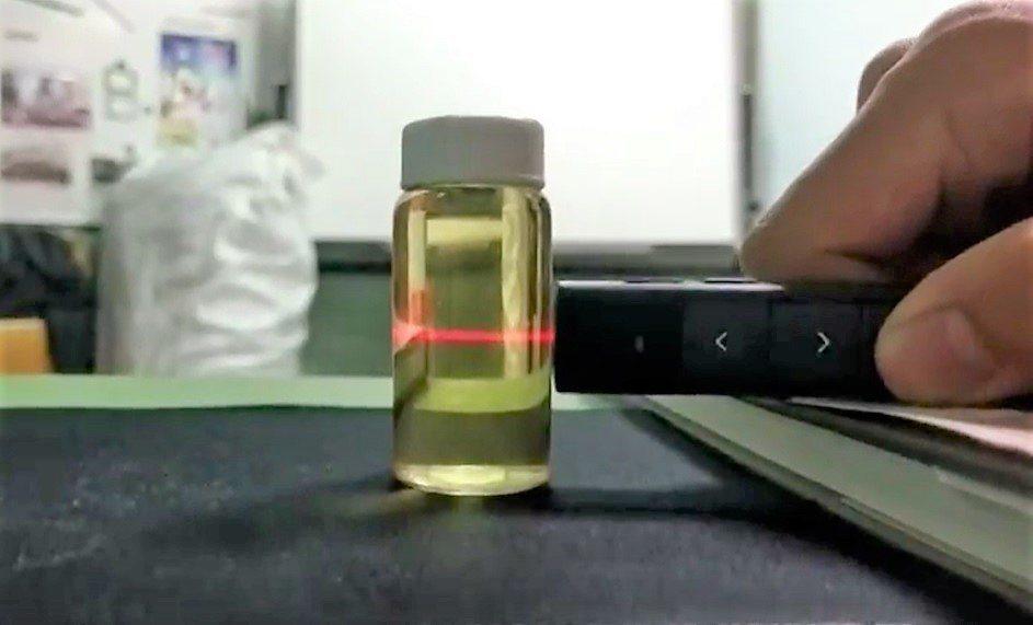 真的威士忌加水透過雷射筆照射,出現紅線「廷得耳效應」,偽酒加水則無。記者卜敏正/...